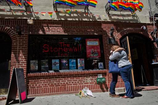 A couple embraces outside the Stonewall Inn, Sunday, June 12, 2016, in New York. New Yorkers are gathering in Manhattan at the historic bar to grieve the deaths of at least 50 people in early Sunday's Florida gay nightclub shooting. The Manhattan bar became a national symbol of gay rights after a 1969 police raid led to violent street riots. (AP Photo/Mary Altaffer)